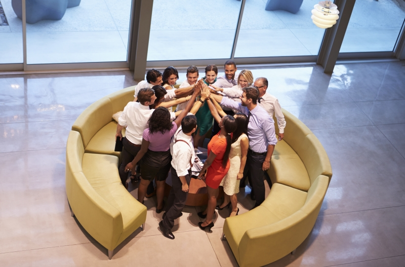 businesspeople-giving-each-other-high-five-in-office-lobby